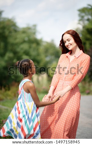 Beaming mother. Beaming mother wearing long dress looking at her cute dark-haired daughter #1497158945