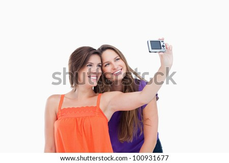 Beaming teenager taking a photo of herself and a smiling friend