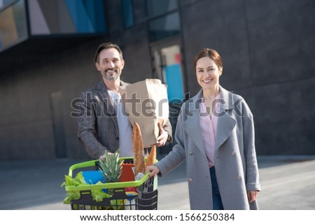 Beaming wife. Beaming wife standing near her loving husband after buying foods at the weekend #1566250384