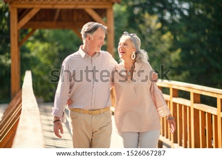 Beaming wife. Beaming wife wearing stylish earrings laughing while walking with her man #1526067287