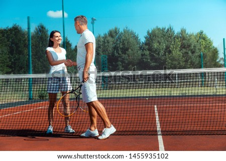 Beaming wife. Beaming wife wearing white t-shirt feeling happy after playing tennis with husband #1455935102
