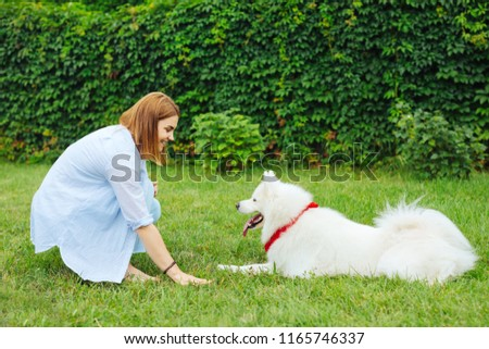 Beaming woman. Beaming woman feeling entertained while enjoying the process of training her dog greatly #1165746337
