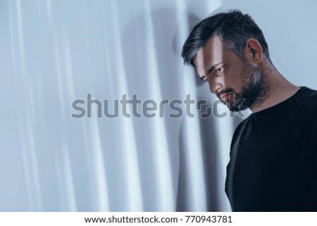 Beams of light shining on depressed man with black rings around his eyes
