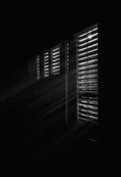 Beams of sunlight through old wooden blinds. Light coming through windows of an old abandoned house, black and white image.