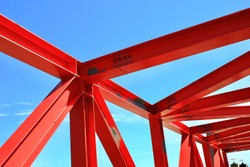 beams of the red bridge are made of steel on blue sky background