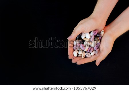 Beans. Handful of multicolored beans in female hands on a black background Сток-фото ©