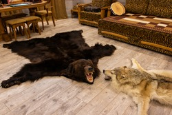 bear and wolf skins on the floor in the hunter's room