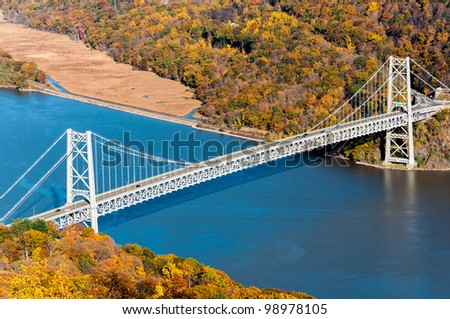 Bear Mountain bridge aerial view in Autumn with colorful trees in forest over Hudson River in New York State. - stock photo