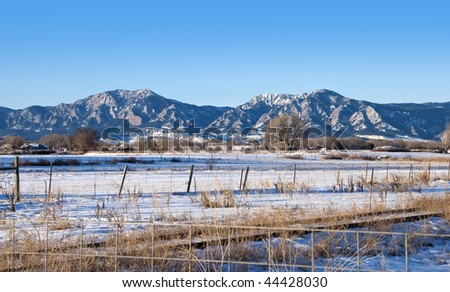 Bear Peak, Green Mountain and the Flatirons Mountains above Boulder, Colorado where prairie meets Rockies, on a sunny winter day with snow, fences and an old railroad track - stock photo
