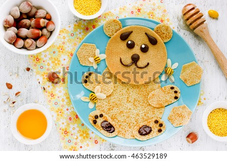 Bear-shaped pancakes with honey and nuts - creative idea for children breakfast, funny food art for kids, edible picture on plate top view