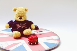 Bear wears unionjacks sweater is sitting on white background with England theme, London red bus .