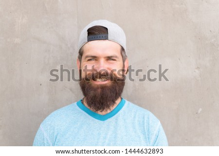 Beard divides the boys from the men. Happy caucasian guy wearing beard on grey wall. Bearded man smiling with stylish mustache and beard shape. Unshaven hipster with textured beard hair outdoor.