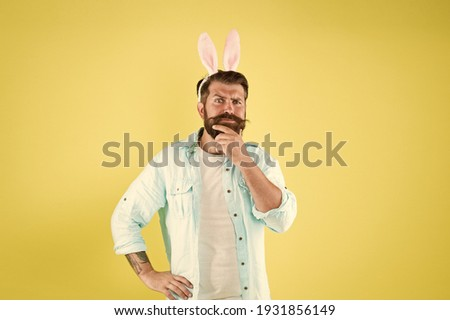 Beard for your face shape. Easter rabbit touch beard yellow background. Bearded man with stylish beard wear bunny ears. Mens grooming. Barbers salon. Barbershop. Adding care to your beard hair.