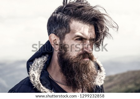 beard. Lumberjack man. bearded man, long beard, brutal caucasian hipster with moustache, unshaven guy with stylish hair getting beards haircut on windy mountain top on natural cloudy sky