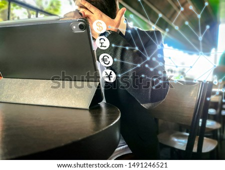 bearded adult rich businessman smoking and using his pro tablet in the cafe holographic economy currency icons #1491246521