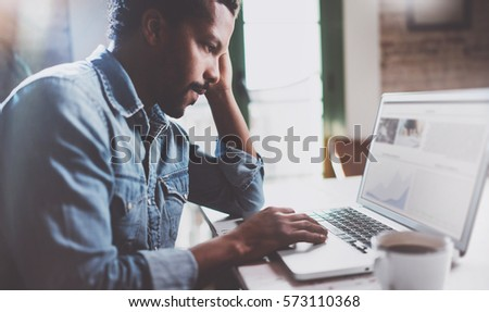 Bearded African man working on laptop while spending time at home.Concept of young business people using mobile devices.Blurred information notebook screen.Selective focus