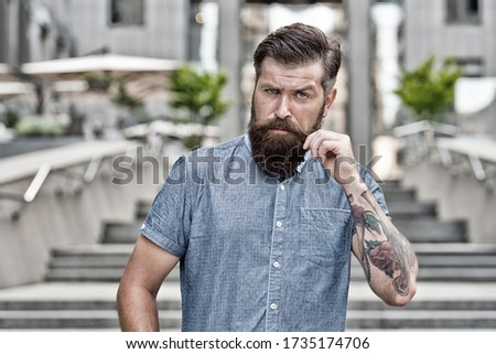 Bearded and brutal. Bearded man urban outdoor. Hipster with bearded look. Shaving salon. Beard barber. Barbershop. Skincare. Haircare. Beard products. Bring more care for bearded face, vintage filter.
