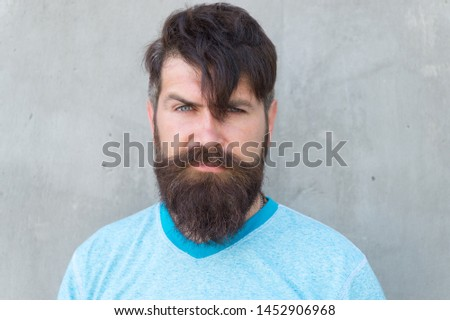 Bearded and shaggy. Bearded man with stylish haircut on grey wall. Unshaven caucasian guy wearing thick mustache and beard hair on bearded face. Brutal hipster in bearded style.