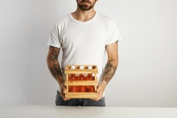 Bearded and tattooed man holding a small crate with six unmarked glass bottles of craft lager beer drink against white wall background