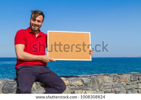 Bearded attractive inviting young man holding a framed blank corkboard in blue sky