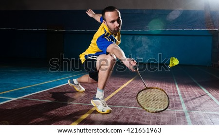 Bearded  badminton player in sport outfit reaching for a shuttle with a racket swing. Artistic studio lighting and lens flare effect.
