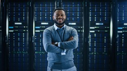 Bearded Black IT Engineer Standing and Posing with Crossed Arms in the Middle of a Working Data Center Server Room with Server Computers Working on a Rack.