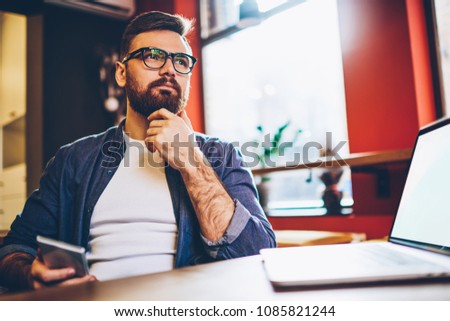 Bearded blogger with smartphone in hands thinking on new ideas for publication on website sitting with laptop device in coworking.Contemplative young man pondering on developing own internet business