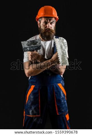 Bearded builder isolated on black background. Bearded man worker with beard, building helmet, hard hat. Plastering tools. Tool, trowel, handyman, man builder. Mason tools, builder.