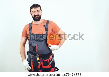 Bearded builder man. House renovation service. Professional builder with tools. Handyman with a tool belt. Engineer builder in uniform. Man builder hard hat. Building improvement and renovation.