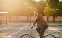 Bearded Businessman in business suit riding on retro bicycle to work on urban street in the morning on sunset