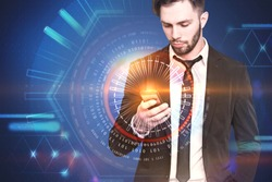 Bearded businessman in suit and tie holding smartphone looking at its screen. Blue background with immersive interface infographics. Toned image double exposure mock up