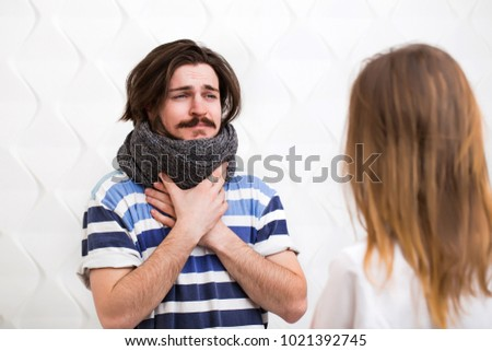 Bearded caucasian ill teenager with gray scarf around the neck visits the doctor #1021392745