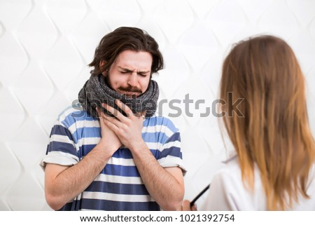 Bearded caucasian ill teenager with gray scarf around the neck visits the doctor #1021392754
