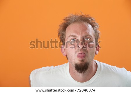 Bearded Caucasian man on orange background sticks out his tongue