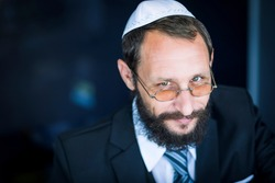 Bearded Charming Jewish man in white Yarmulke (hat, Kippah) looking with cunning eyes. Emotional expression. Sly bearded Jewish man smiling cunning looking at the camera. Selective focus on the eyes