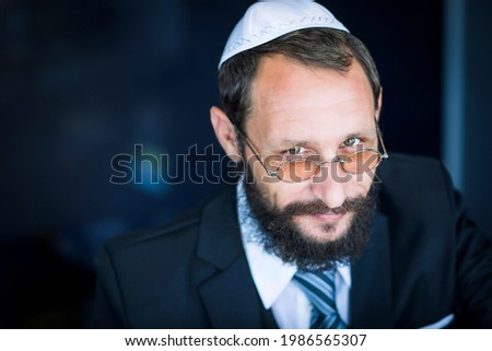 Bearded Charming Jewish man in white Yarmulke (hat, Kippah) looking with cunning eyes. Emotional expression. Sly bearded Jewish man smiling cunning looking at the camera. Selective focus on the eyes Stock fotó ©