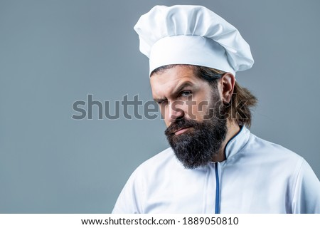 Bearded chef, cooks or baker. Bearded male chefs isolated. Cook hat. Confident bearded male chef in white uniform. Serious cook in white uniform, chef hat. Portrait of a serious chef cook. Stock foto ©
