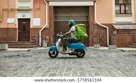 Bearded delivery man in helmet with thermo bag or backpack riding a motor scooter along the city, delivering food. Courier, delivery service concept. Horizontal shot. Side view