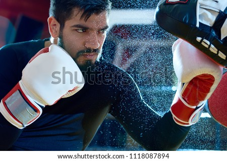 Bearded determined man boxing on ring with trainer while punching focus mitts in water drops.  #1118087894