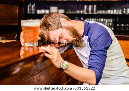 bearded drunk man sleeps with Barney table with a glass of beer #501351322