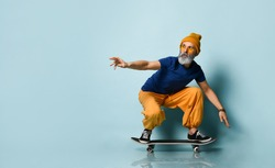 Bearded elderly man in t-shirt, sunglasses, orange pants and hat, gumshoes, bracelets. Riding black skateboard, posing against blue studio background. Fashion, style, sport. Full length, copy space
