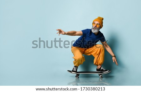 Bearded elderly man in t-shirt, sunglasses, orange pants and hat, gumshoes, bracelets. Riding black skateboard, posing against blue studio background. Fashion, style, sport. Full length, copy space stock photo