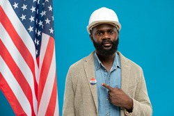Bearded engineer of African ethnicity standing against stars-and-stripes flag and pointing at vote insignia on collar of his jacket