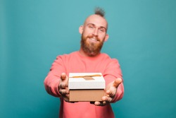 Bearded european man in casual peach isolated on turquoise background happy holds out gift box to camera