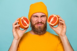 Bearded european man in yellow shirt isolated on turquoise background holding grapefruit tastes, wrinkles from bitterness