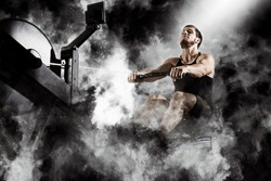 Bearded fit man using rowing machine at functional training gym