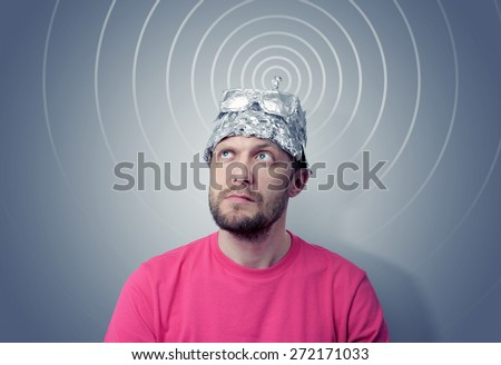 Bearded funny man in a cap of aluminum foil sends signals. Concept art phobias