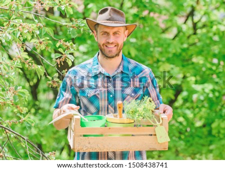 Bearded gardener guy hold box with flower pot and hoe gardening tool. Gardening advice from professional. Gardening expert tips. Garden care. Mature farmer man planting plants. Planting season.