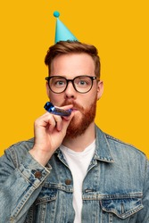 Bearded guy in glasses and party cap looking at camera and blowing noisemaker during birthday celebration against yellow background