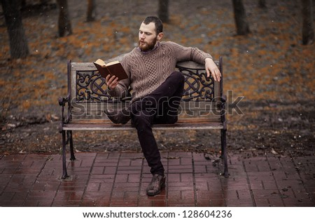 bearded guy reading a book in the park